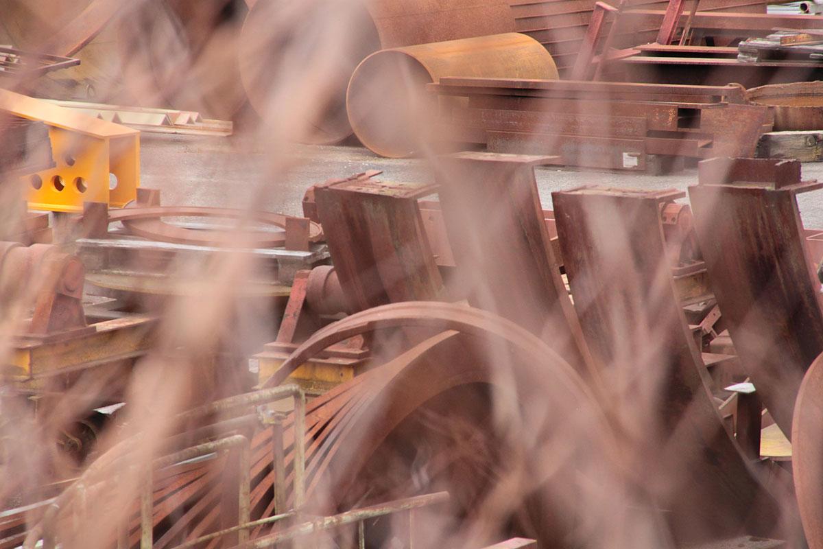 Suchbild Nummer_17: Blick durch Gestrüpp auf das Gelände der Firma Leffer